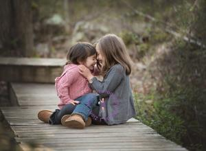 Two girls sitting and giggling and hugging outdoors.